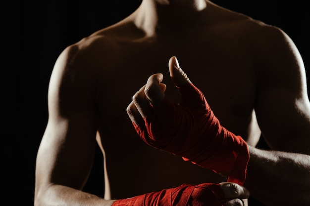 Close up boxer bandaging hands