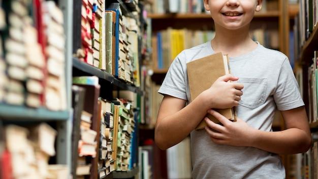 本棚の間のクローズアップの少年