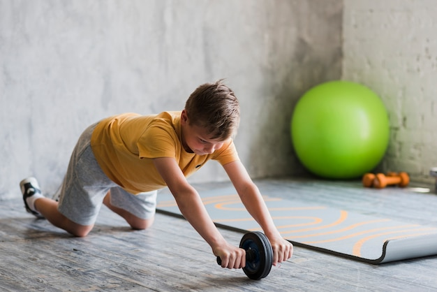 Close-up of a boy doing ab wheel rollout exercise on hardwood floor