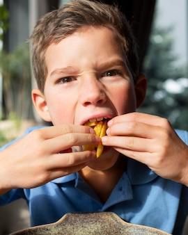 フライドポテトを食べる少年をクローズアップ