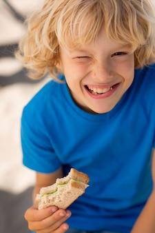 サンドイッチを食べる男の子をクローズアップ