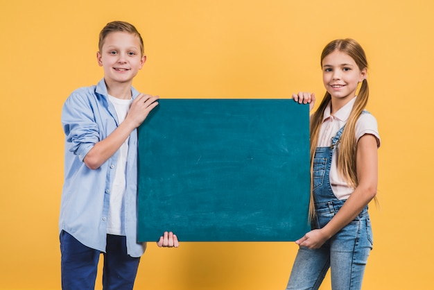 Close-up of a boy and girl holding green chalkboard against yellow backdrop