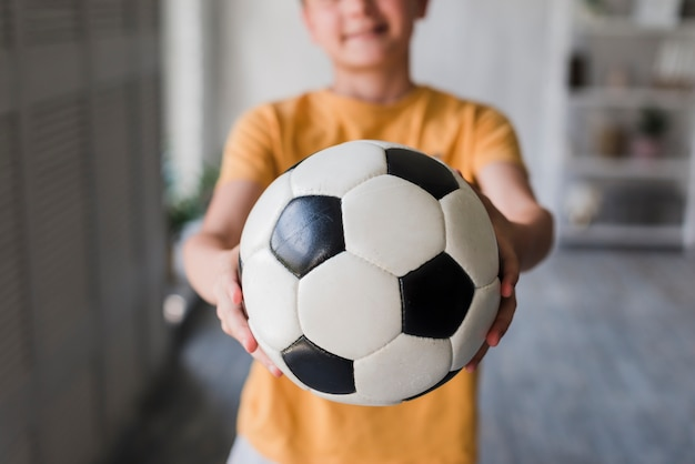 Close-up of boy giving soccer ball toward camera