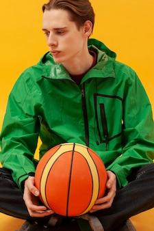 Мальчик крупным планом держит баскетбольный мяч