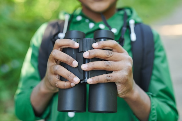 Close-up of boy holding binoculars while travelling outdoors