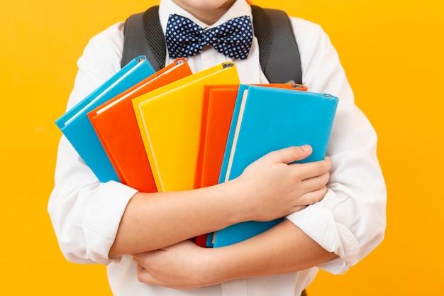 Мальчик крупным планом держит книги