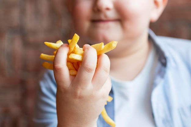 Close up boy holding french fries
