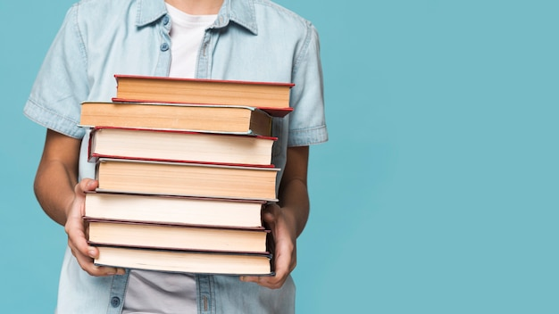 Крупным планом мальчик держит стопку книг
