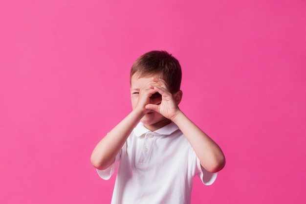 Close-up of boy looking through hand as binoculars over pink wall background