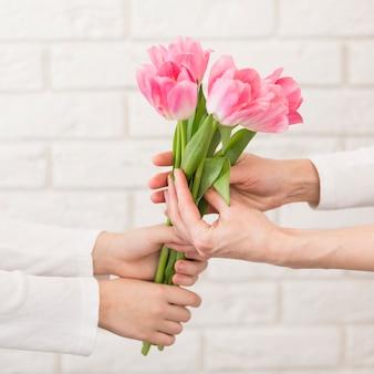 Мальчик крупным планом, предлагая цветы матери