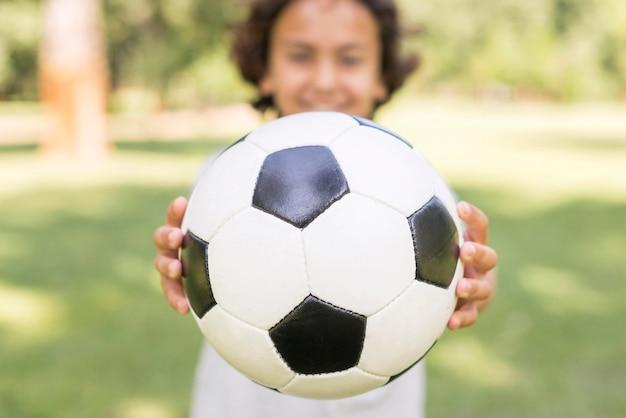 Ragazzo del primo piano che gioca con la palla di calcio