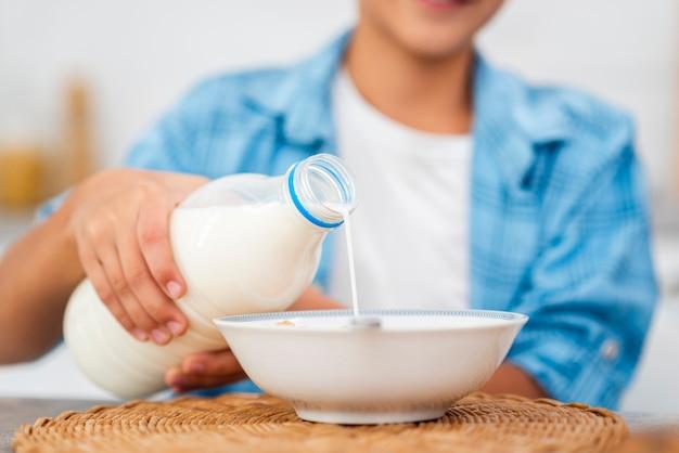 Мальчик крупным планом наливает молоко над хлопьями