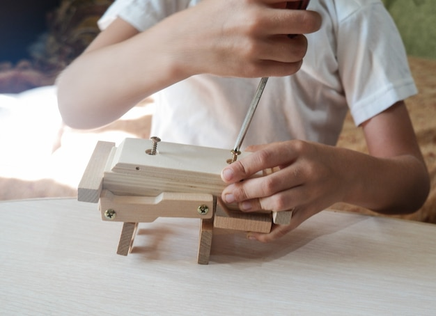 Close-up of a boy's hand assembles a wooden toy car with a screwdriver on a wooden table at home.