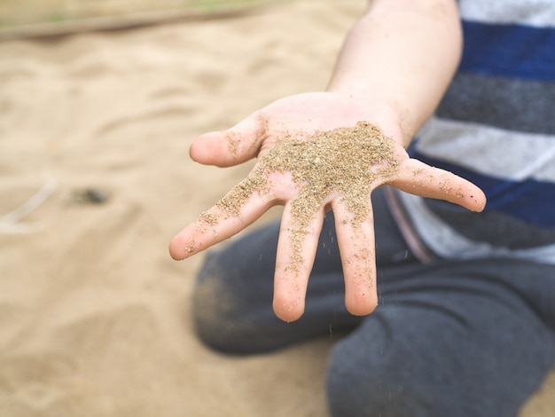 Close up a boy's hand holding sand on playground