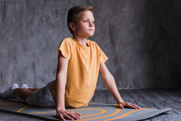Close-up of a boy stretching on exercise mat in front of concrete wall