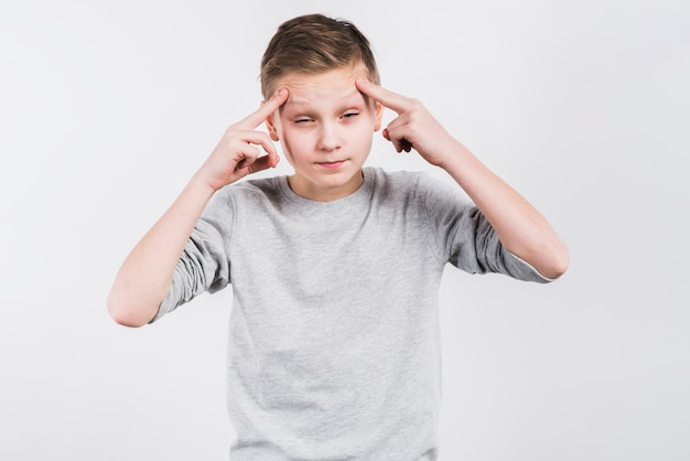 Close-up of a boy suffering from headache against grey background