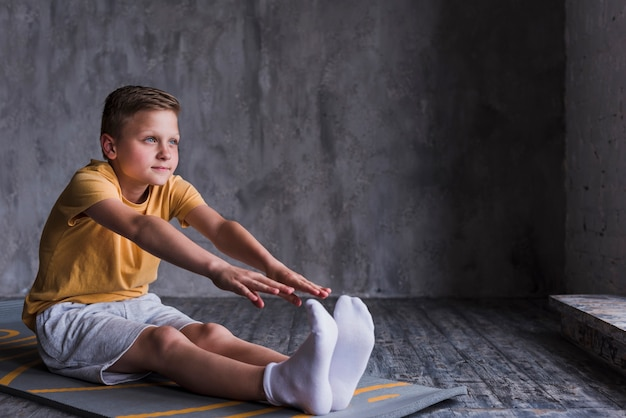 Close-up of a boy wearing white socks stretching his hand
