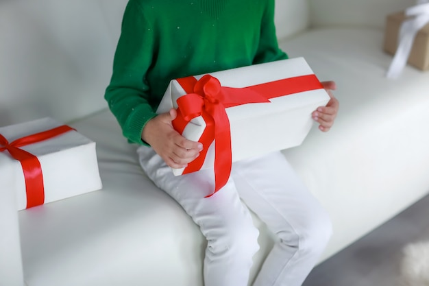 Close-up of a boy on a white sofa surrounded by gift boxes in white packaging and a red ribbon