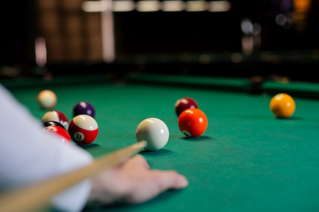 Close-up boy with pool cue playing billiard