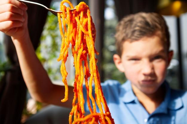 スパゲッティで男の子をクローズアップ