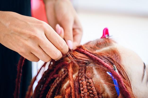 Close up of braiding process plait with colored kanekalon beauty salon services girl hairdresser wea...
