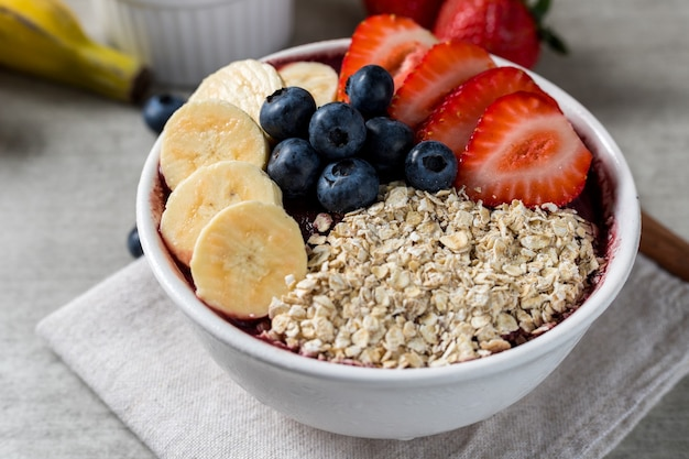Закройте вверх по бразильской замороженной миске мороженого из ягод айсай с клубникой, бананами, черникой и овсяными хлопьями. с фруктами на деревянных фоне. вид спереди летнее меню