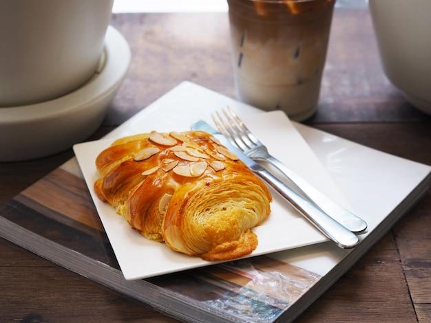 本の白い皿とカフェでアイスラテコーヒーのグラスの上にフォークとナイフでパンアーモンドを閉じます。朝の朝食またはコーヒーブレイク。