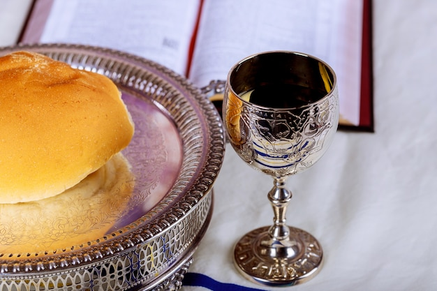 Close up of bread and a cup of red wine on wooden table for communion