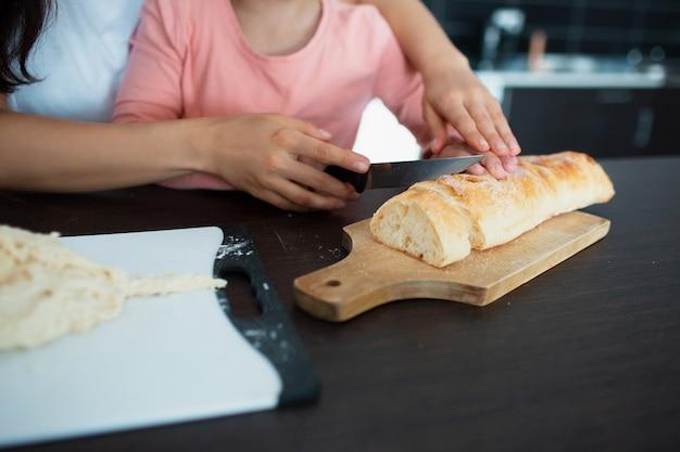 Нож хлеба конца-вверх и руки матери и дочери в кухне.