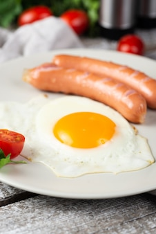 Close-up of breakfast egg and sausages on plate with tomatoes