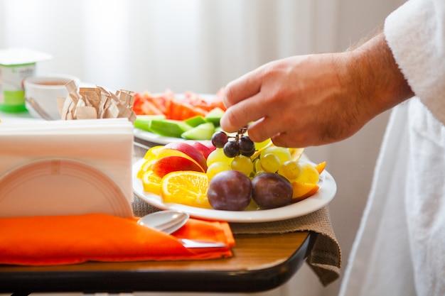 Крупным планом завтрак с фруктами апельсинов, яблок, винограда, сливы, тарелка с помидорами, огурцами