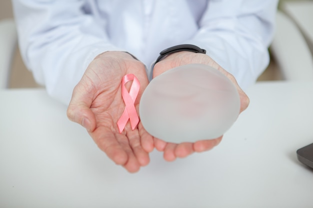 Close up of breast cancer awareness pink ribbon and silicone breast implant in the hands of unrecognizable doctor