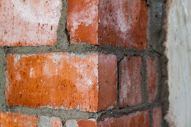 Close up of bricklaying industrial installing bricks on construction site wall