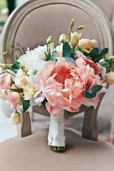 Close-up bridal bouquet of fresh spring and summer flowers in pastel colors stand on a classic chair