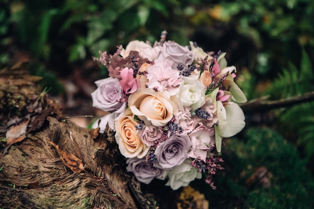 Close-up bridal bouquet of roses in lilac pink on a blurred background of forest and moss, selective focus