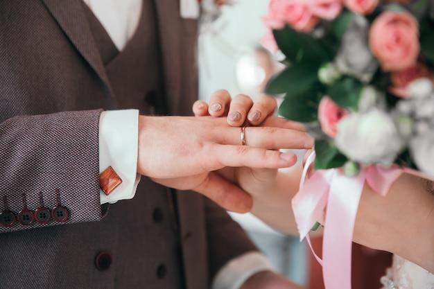 Закройте вверх. жених и невеста обмениваются обручальными кольцами. праздники и события
