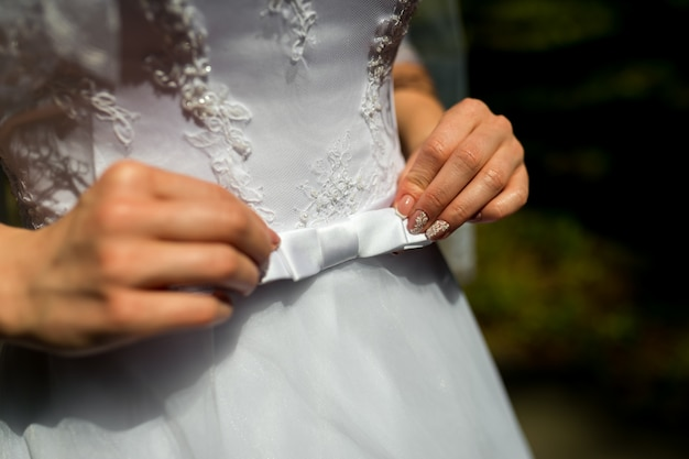 A close up of a bride dress with a large silk bow