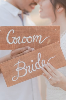 Close up of the bride and groom holding sign wooden plate outdoors. romantic couple and love concept