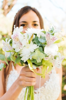 Close-up of a bride holding white flower bouquet in front of her face
