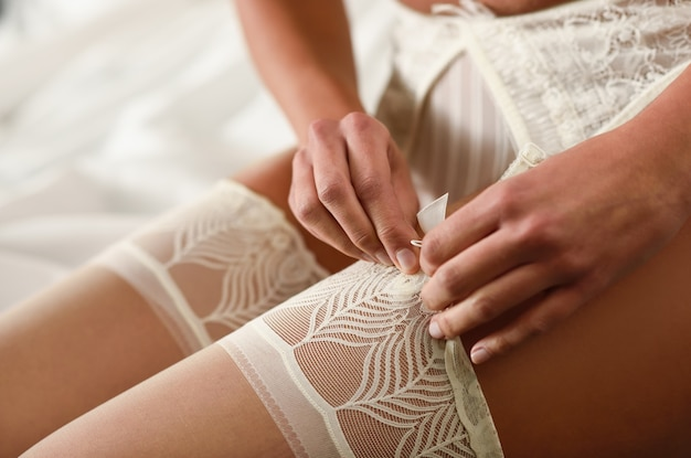 Close-up of bride putting on stockings