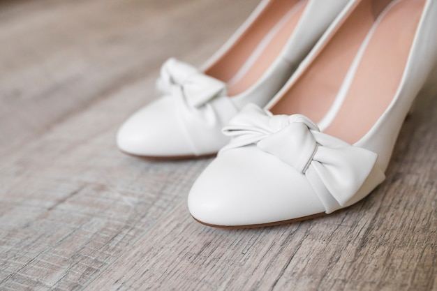 Close-up of bride's dress shoes on wooden textured background