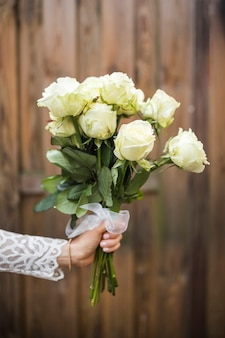 Close-up of bride's hand holding bouquet of roses against wooden backdrop