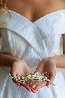 Close-up of bride's hands with hair ornament for wedding hairstyle.