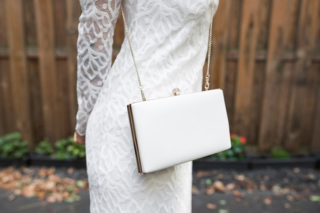 Close-up of bride with elegant white clutch at outdoors