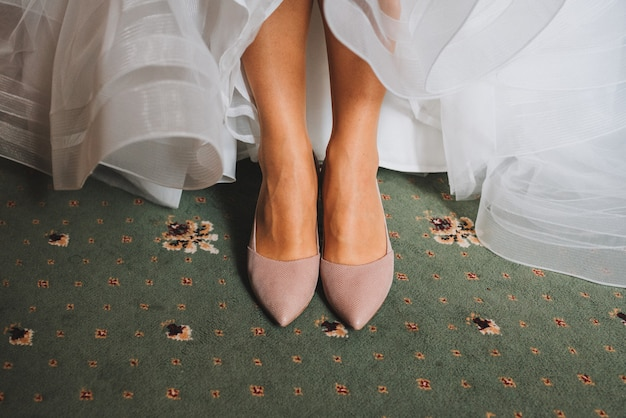 Close up of brides feet wearing elegant shoes and wedding dress