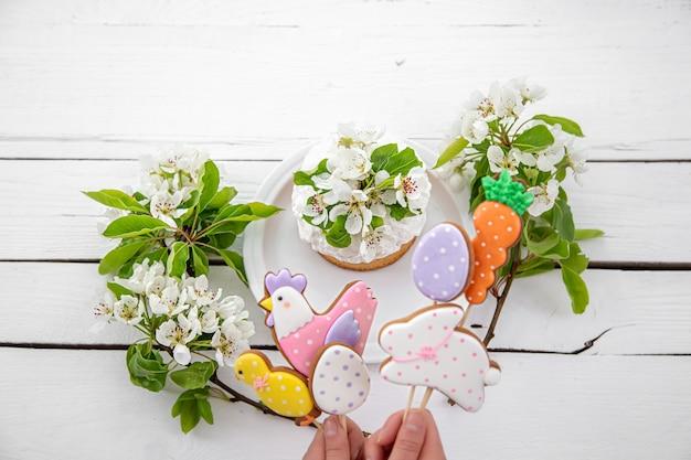 Primo piano dei biscotti luminosi del pan di zenzero di pasqua sui bastoni e sulla torta di pasqua decorata con i fiori. il concetto di arredamento per le vacanze di pasqua.