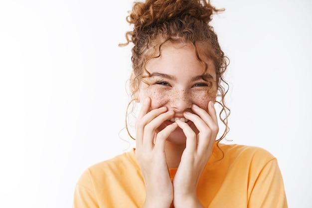 Primo piano brillante emotiva felice giovane sorridente ragazza rossa disordinata chignon ridere coprire bocca ridacchiando durante un incontro serio importante non può tenere il sorriso, in piedi eccitato sfondo bianco giocoso