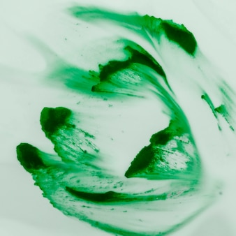 Close-up of bright green watercolor brush strokes painted on white surface