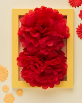 Close-up of bright red paper flower and photo frame