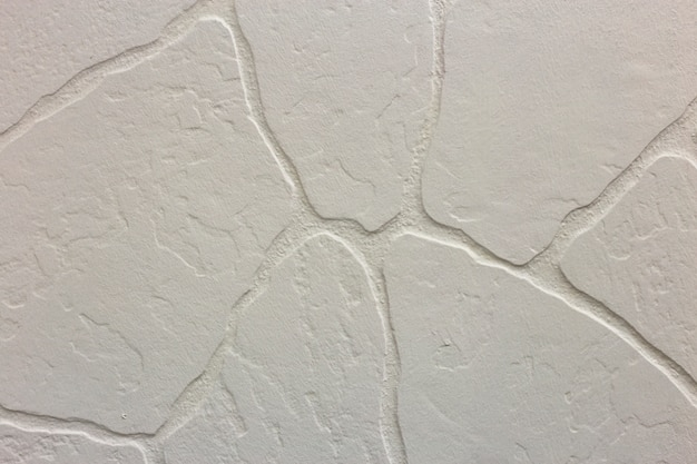 Close-up of bright white plastered uneven stucco wall. abstract texture, chaotic copy space background. decorative grunge space.